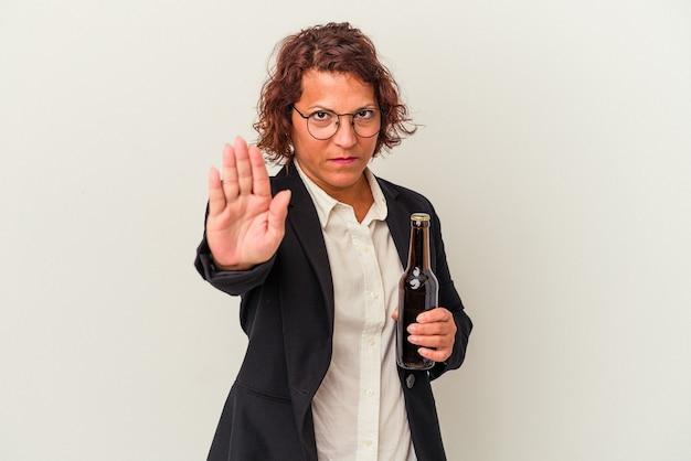 Lateinische geschäftsfrau mittleren alters, die ein bier isoliert auf weißem hintergrund hält, das mit ausgestreckter hand steht und ein stoppschild zeigt, um sie zu verhindern.