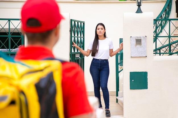 Lateinische hübsche frau, die am eingang steht und kurier wartet. unscharfer lieferbote in roter mütze und hemd mit gelbem thermorucksack und lieferauftrag. lieferservice und postkonzept