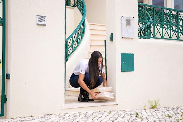 Lateinische schöne frau, die ordnung vom eingang erhält. junge brünette kundin hockt, lächelt und nimmt pappkartons mit beiden händen. lieferservice und online-shopping-konzept