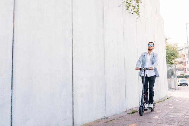 Lateinischer erwachsener mann mit der sonnenbrille, gut gekleidet und fahren elektrischen roller auf der straße mit einem weißen blinden hintergrund