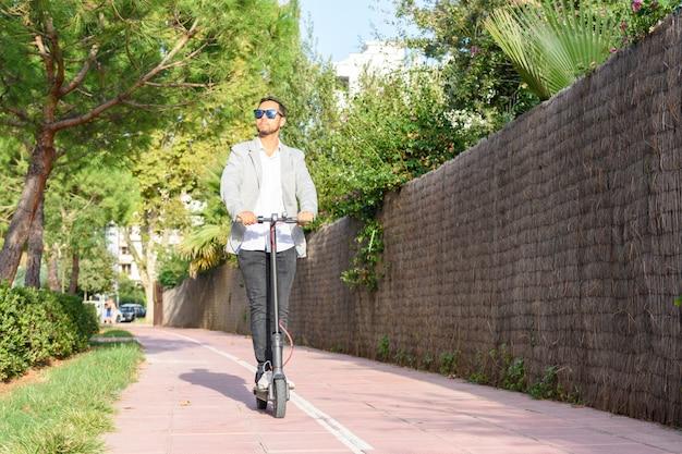 Lateinischer erwachsener mann mit sonnenbrille, gut gekleidet und fahren elektrischen roller auf der straße
