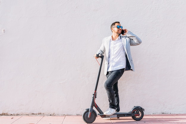 Lateinischer erwachsener mann mit sonnenbrille, gut gekleidetem und elektrischem roller sprechend an seinem handy, der auf der straße mit einem weißen wandhintergrund sitzt