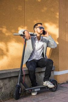 Lateinischer erwachsener mann mit sonnenbrille, gut gekleidetem und elektrischem roller sprechend an seinem handy, der auf der straße sitzt