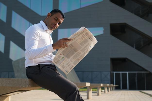 Lateinischer geschäftsmann, der zeitung außerhalb des büros liest