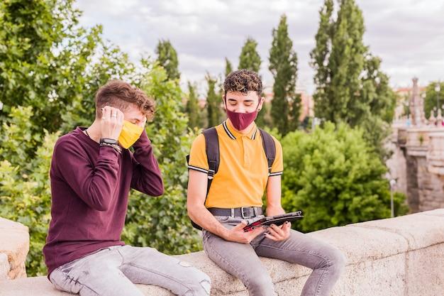 Lateinischer junger mann und nicht binäre transgender-freunde, die technologie für soziale distanz in neuer normalität verwenden using