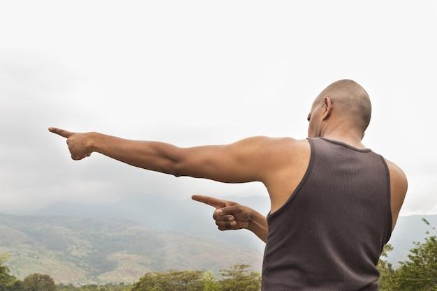 Lateinischer kolumbianischer afroamerikaner fitness-mann, der berge beobachtet