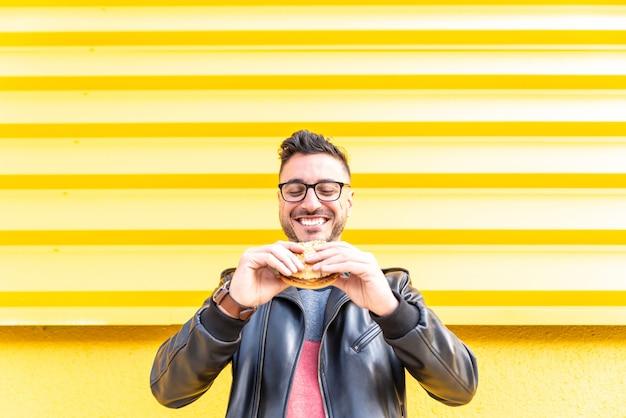Lateinischer mann, der draußen einen hamburger isst.