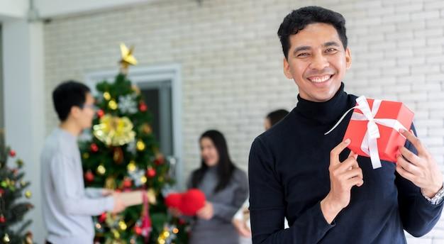 Lateinischer mann, der mit dem halten der roten geschenkbox im wohnzimmer mit gruppe freunden für weihnachtsfestfeier heute abend konzept lächelt