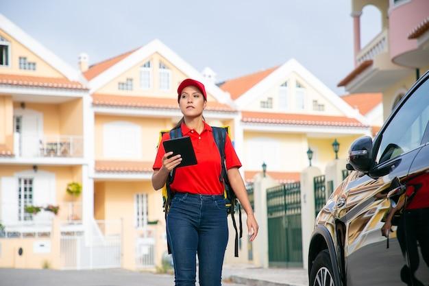 Lateinischer weiblicher kurier, der tablette mit adresse geht und hält. fokussierte lieferfrau, die expressbestellung im gelben thermorucksack liefert.