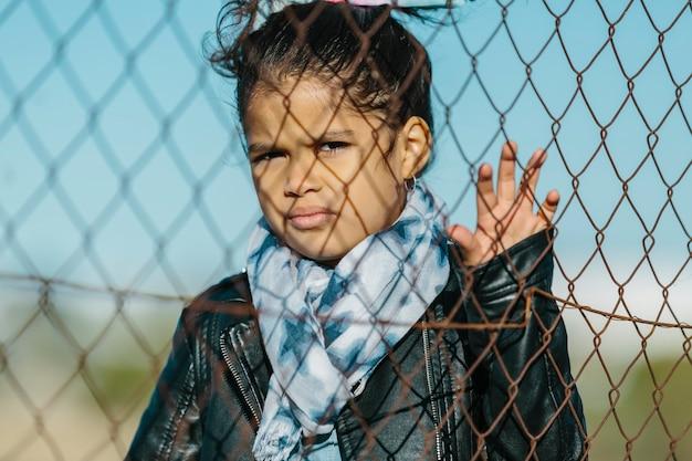 Lateinisches junges mädchen, das die kamera mit einem ernsten und wütenden ausdruck betrachtet, mit der hand, die auf dem zaun, hinter einem zaun, in einem blauen himmelhintergrund ruht. kindheits- und bildungskonzept.