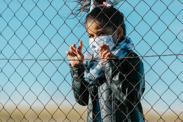 Lateinisches junges mädchen, das eine maske trägt und die kamera mit einem ernsten ausdruck hinter einem zaun in einem hintergrund des blauen himmels betrachtet. kindheits- und coronavirus-konzept.