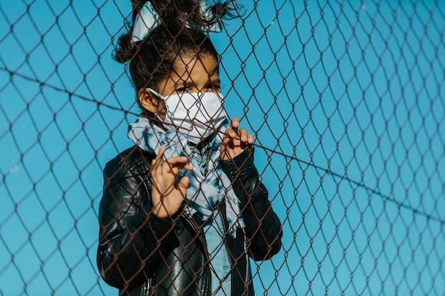 Lateinisches junges mädchen, das eine maske trägt und die kamera mit einem ernsten ausdruck hinter einem zaun in einem hintergrund des blauen himmels betrachtet. sie hat ihre hände am zaun. kindheits- und coronavirus-konzept.