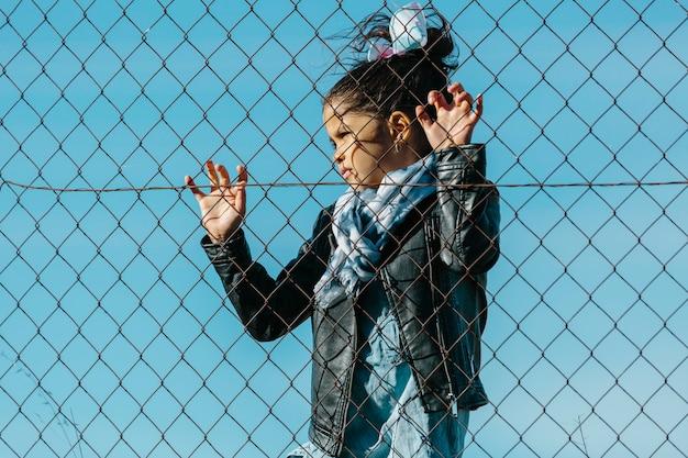 Lateinisches junges mädchen, das weg mit einem dramatischen und traurigen ausdruck, hinter einem zaun, in einem blauen himmelhintergrund schaut. kindheits- und bildungskonzept.