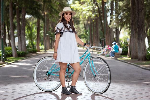 Lateinisches mädchen mit einem fahrrad mit kleid und hut in einem park mit bäumen und blumen