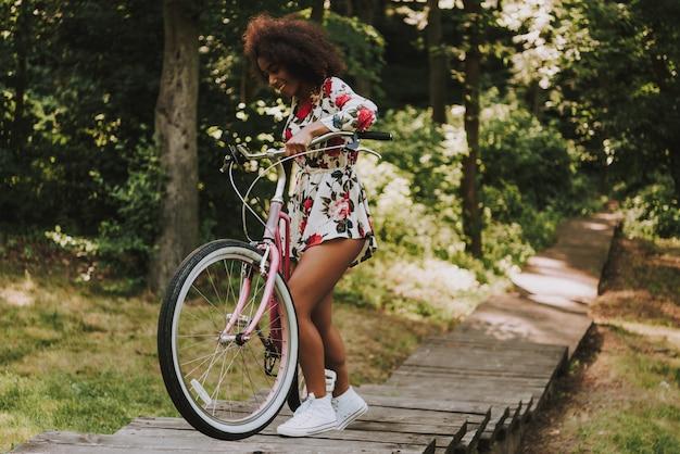 Lateinisches mädchen rollt das fahrrad auf hölzernem gehweg.