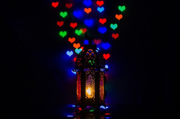 Laterne mit bunten bokeh-lichtern in liebesform für islamisches neujahr und ramadan kareem-konzept.