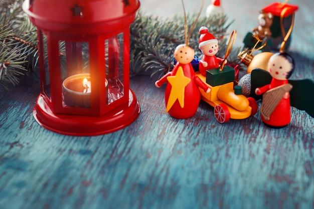 Laterne mit einer kerze, weihnachtsbaumasten und weihnachtsspielzeug