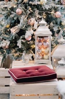 Laterne mit feiertagskugeln auf geschmücktem weihnachtsbaum im wohnzimmerinnenraum