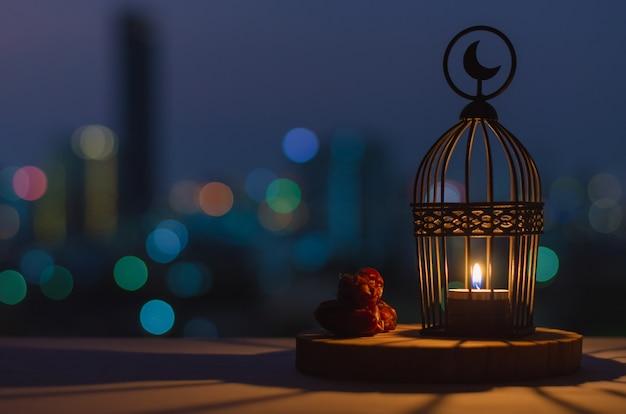Laterne mit mond-symbol oben und dattelfrucht auf holztablett mit bunten stadt-bokeh-lichtern für das muslimische fest des heiligen monats ramadan kareem.