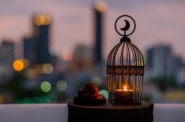 Laterne mit mond-symbol und dattelfrucht mit stadt-bokeh-lichtern für ramadan kareem.
