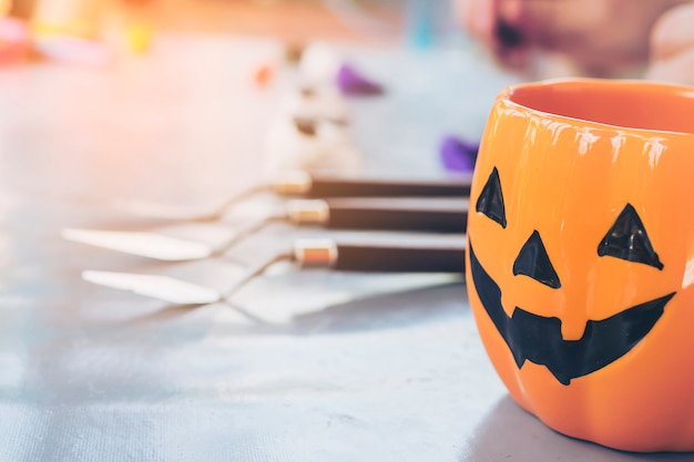 Laternengesichtsbecher halloween-steckfassung o über dem unscharfen jungen, der lehmspielzeughintergrund gestaltet