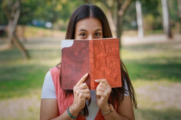 Latina-frau bedeckt ihr gesicht mit einem buch im park