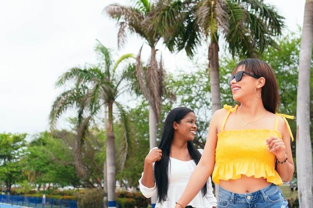 Latina-freunde fühlen sich gut, wenn sie die straße entlang gehen. urbanes äußeres im sommer.
