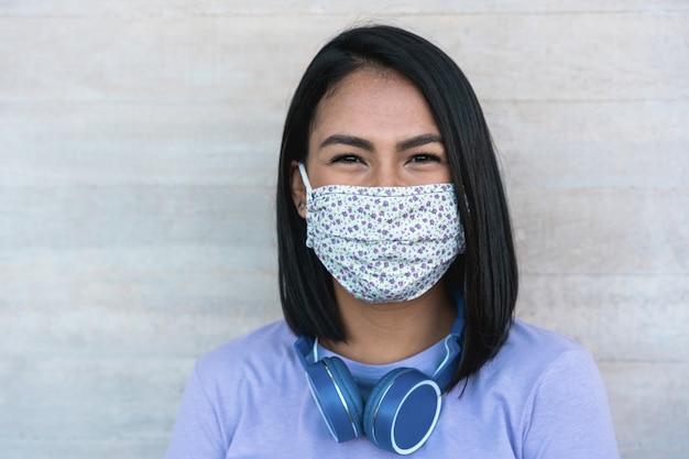 Lating tausendjähriges mädchen lächelnd beim tragen der gesichtsschutzmaske