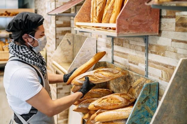 Latino-bäcker, der frisch gebackenes brot mit einer schützenden gesichtsmaske beiseite legt