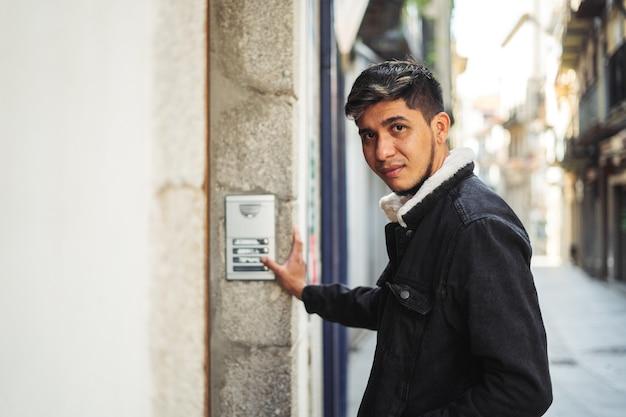 Latino-mann klingelt an einer gebäudetür