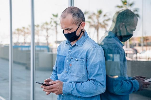 Latino-mann mittleren alters mit maske konsultiert das smartphone