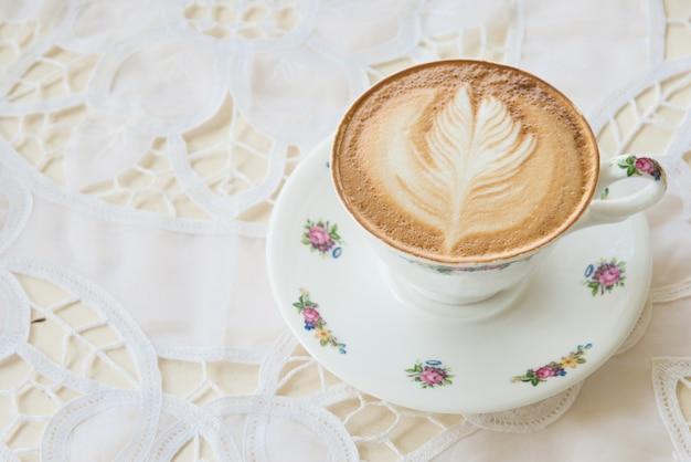 Latte art coffee in der weinleseschale auf dem tisch in der kaffeestube