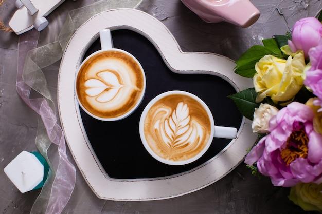 Latte art in zwei tassen cappuccino auf dem tablett in herzform. schönen morgen valentinstag paar