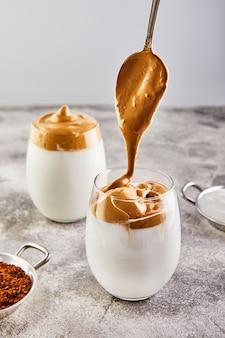 Latte espresso mit kaffeeschaum in hohem glas und milch