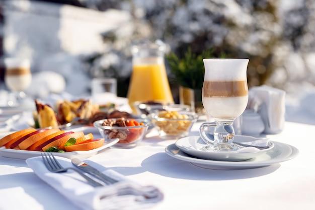Latte kaffee auf der terrasse vor dem restaurant gegen den schnee