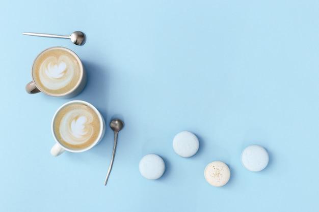 Latte kaffeekunst in zwei großen bechern und süßen makronen auf sanftem blauem hintergrund. morgen heißes getränk und dessert für ein paar leute. flach liegen.