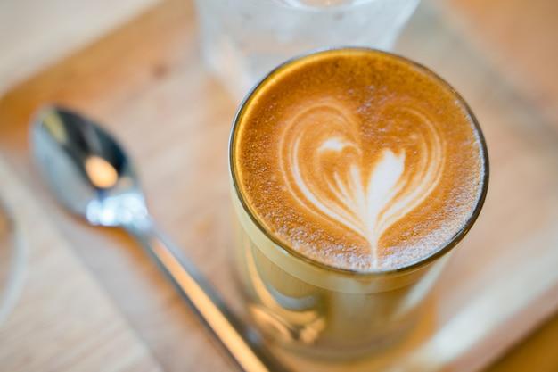 Latte kaffeekunst serviert mit einem glas wasser
