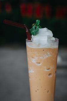 Latte mit schlagsahne gemischt, beschneidungspfad. eiskaffeemischmaschine in einem glas.