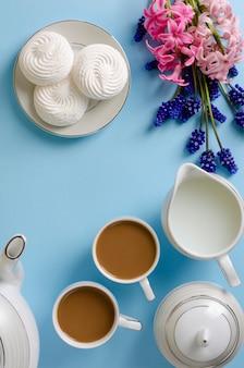 Latte, weiße meringen, milchglas auf dem blauen pastellhintergrund verziert mit muscari- und hyazinthenblumen.