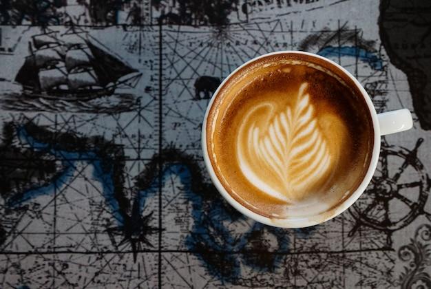 Lattee kaffee auf weltkartehintergrund und copyspace, getränk und getränkkonzept.