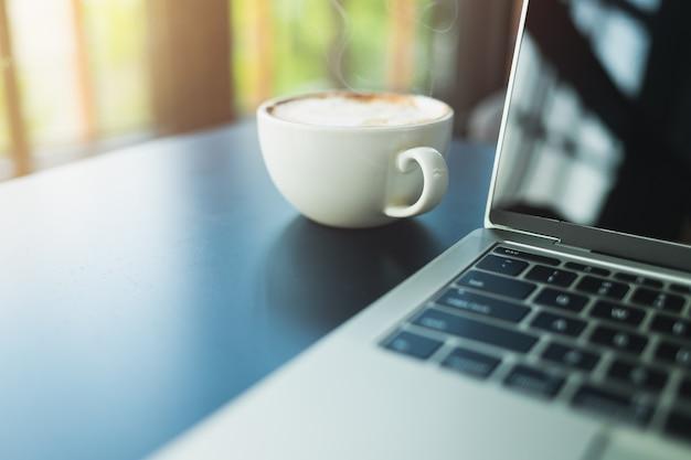 Lattekaffee in einer weißen kaffeetasse und in einer laptopseite auf einem schwarzen holztisch