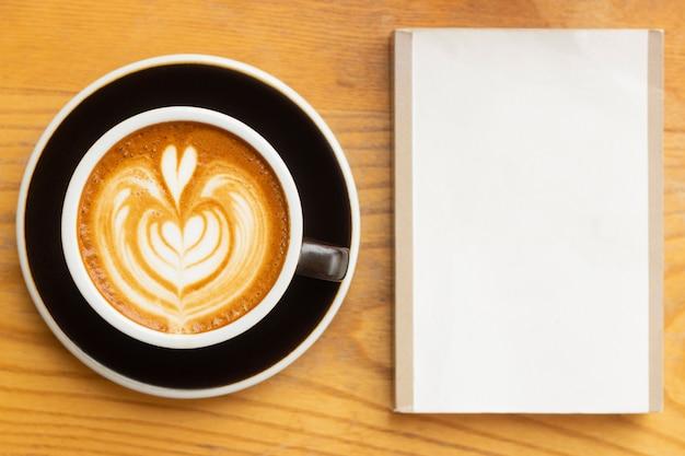 Lattekaffee und leerer raum buchen auf hölzerner tabelle