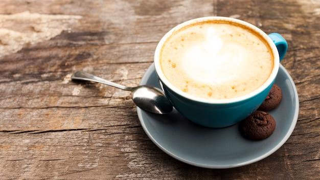 Lattekaffeetasse mit köstlichen plätzchen auf hölzernem schreibtisch