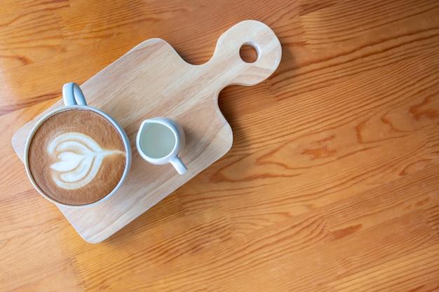 Lattekaffeetasse mit lattekunst auf holztisch in der kaffeestube.