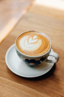 Lattekunst-herzform diente in der keramischen schale auf holztisch.
