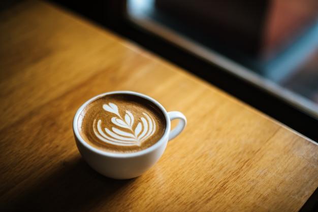 Lattekunst in der kaffeetasse auf der cafétabelle