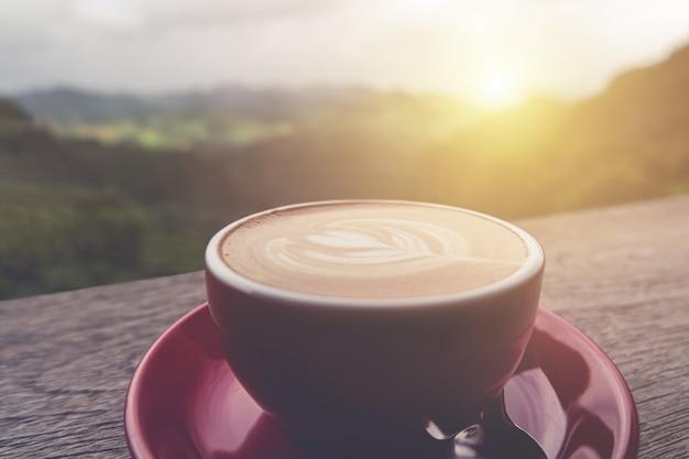 Lattekunst-kaffeetasse auf dem holztisch, ebenenlage