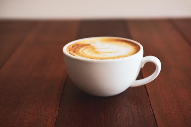 Lattekunstkaffee auf holztisch auf kaffeezeit