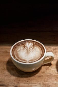 Lattekunstkaffee in der kaffeetasse auf hölzernem schreibtisch im schwarzen