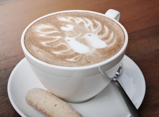 Lattekunstkaffee mit muster und plätzchen mit zwei vögeln in einer weißen schale auf hölzernem hintergrund